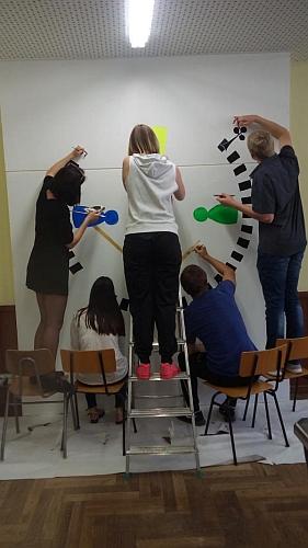 Schüler bringen das von ihnen entwickelte Logo im Spielesaal an